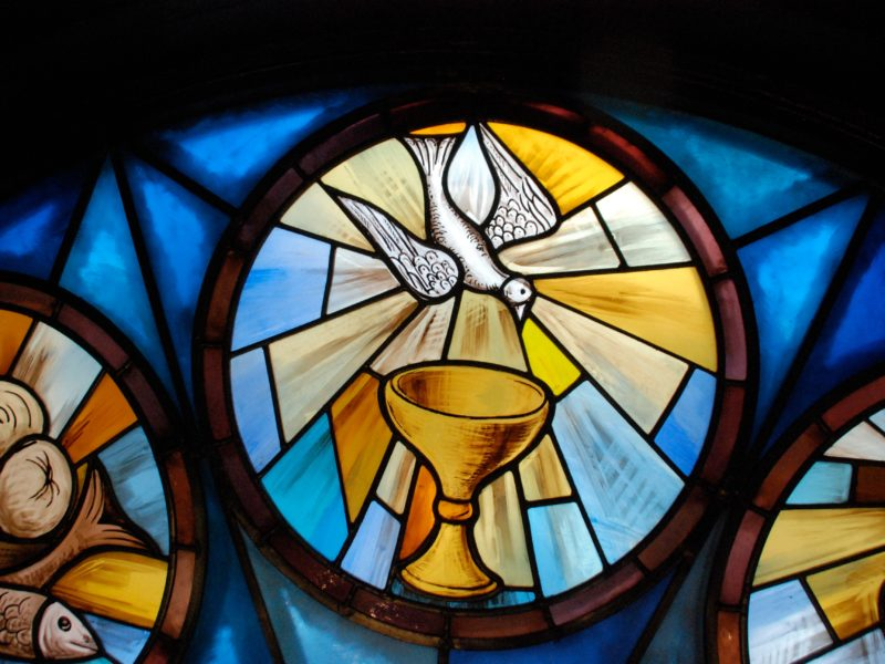 Stained glass window with dove and the Eucharist